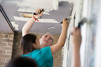 """Members including Megan Laufenberg, center, paint an entryway during """"Circle the City with Service,"""" the Kiwanis Circle K International's 2015 Large Scale Service Project, on Wednesday, June 24, 2015, at the Friendship Westside Center for Excellence in Indianapolis. (Photo by James Brosher)"""