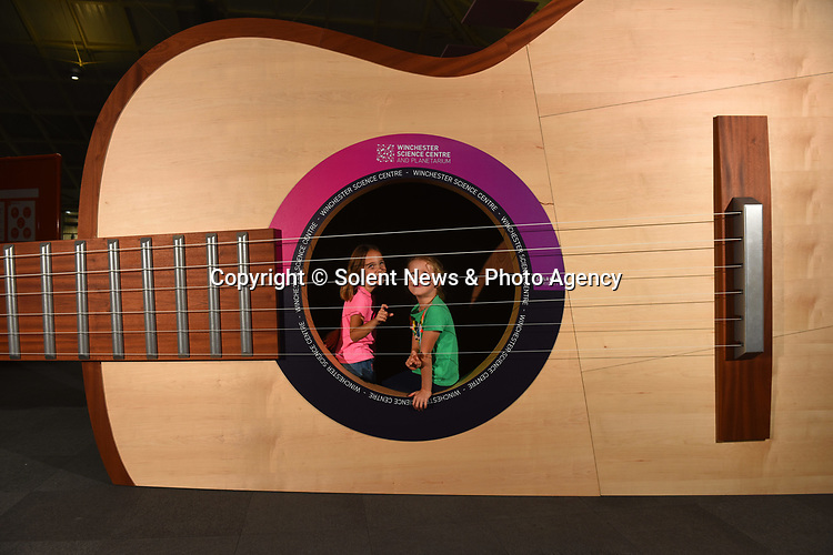 Pictured : Orla Barnaville and Florenza Hellings have a go at playing the giant guitar, a new installation, which will greet visitors to the Winchester Science Museum and Planetarium, Hampshire.<br /> <br /> At over 10 metres long and 3 metres high, the giant interactive installation allows visitors to explore inside its huge body and listen as sounds produced from the strings reverberate inside.<br /> <br /> The strings of the instrument, made from sailing winches and spearfishing line, will need to be 'tuned' regularly as it gets plucked by visitors.<br /> <br /> The biggest single project undertaken at the Science Centre since opening in 2002, a £1.1million development has seen the entire top floor of the two storey venue completely transformed.<br /> <br /> Designed to coincide with the International Year of Sound 2020 and opening this weekend, other installations include an acoustic sonic rocket and smaller table top exhibits including tuning forks and pendulums.<br /> <br /> © Roger Arbon/Solent News & Photo Agency<br /> UK +44 (0) 2380 458800