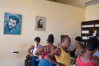 Customers at a pharmacy with Che Guevara portraits on the walls, Trinidad, Sancti Spiritus, Cuba.