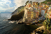 The colorful buildings of Riomaggiore cling to the cliffs on the Ligurian coast in the Cinque Terre region of Italy.