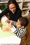 Education preschool 3-4 year olds art activity female teacher talking to boy who is drawing with a marker in each fist vertical
