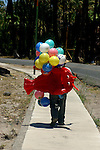 MAN SELLS BALLOONS AND CHILDS FLOAT ALONG THE STREET