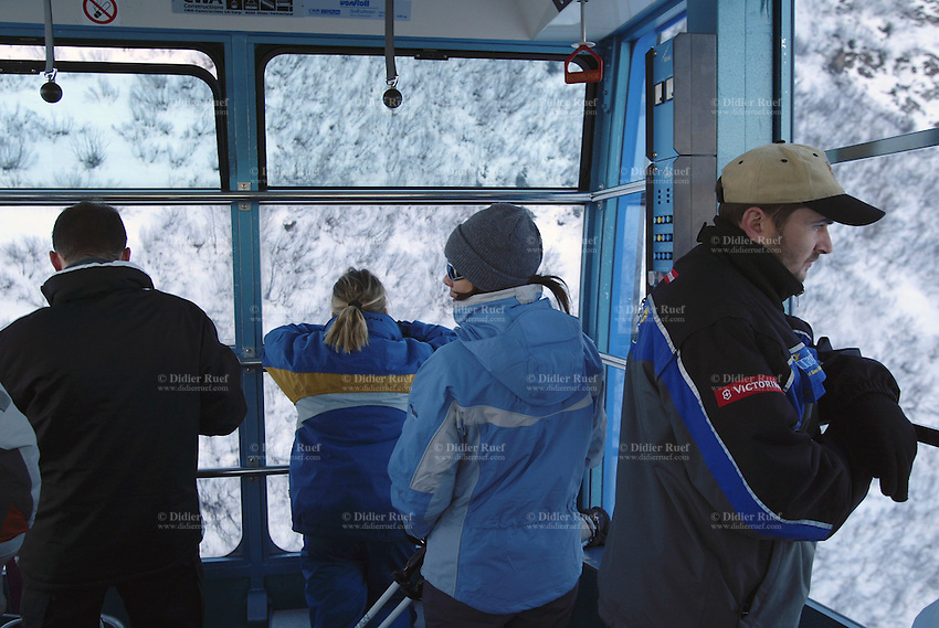 Switzerland. State of Ticino. Airolo. Tourists and skiers use a cable car to access the Peschün ski resort. They look out of the window on the landscape covered with snow. © 2005 Didier Ruef