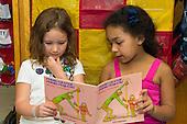 MR / Schenectady, NY. Zoller Elementary School (urban public school). Kindergarten classroom. Two bilingual students read Spanish-language book in class. Left: girl, 6, Hispanic-American; Right: girl, 5; both are native Spanish speakers. MR: Fue3, Cas12. ID: AM-gKw. © Ellen B. Senisi.