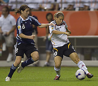 Germany forward (20) Petra Wimbersky is marked by Argentina defender (8) Clarisa Huber. Germany (GER) defeated Argentina (ARG) 11-0 during an opening round Group A match of the FIFA Women's World Cup China 2007 at Shanghai Kongkou Football Stadium, Shanghai, China, on September 10, 2007.