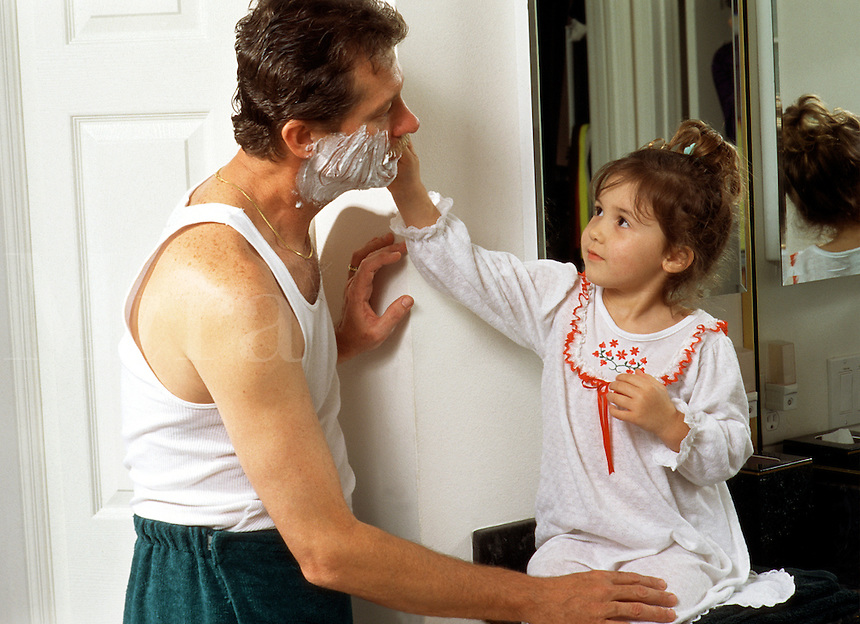 An affectionate family moment of a young daughter helping her father to shave.