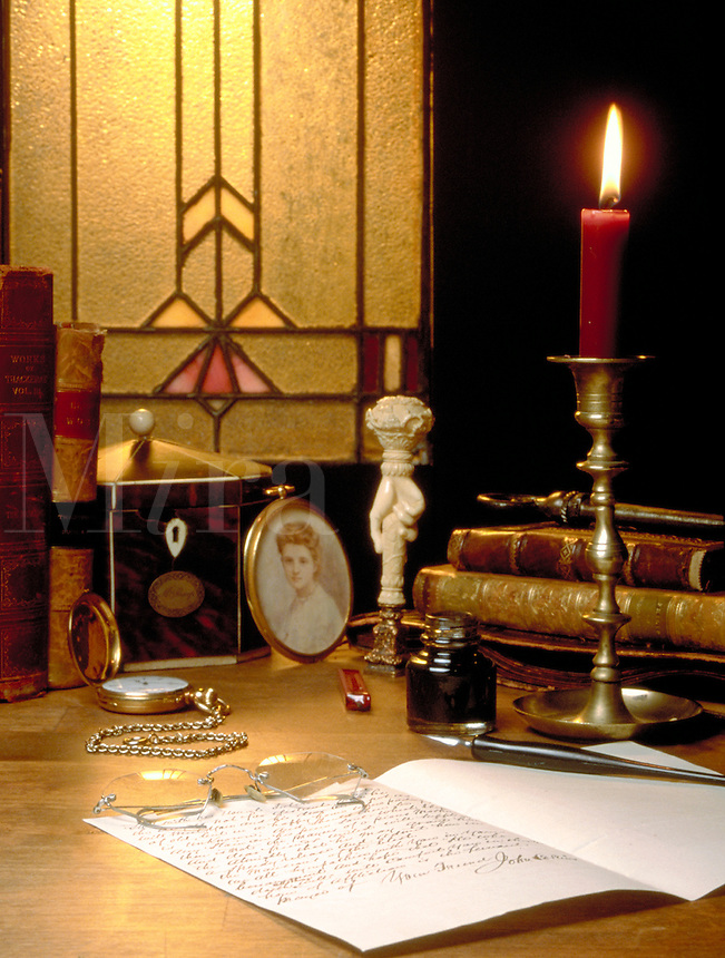 An old desk top with a letter from the 1800's, old books, a candle, and memorabilia on it. antique, period, vintage, still life.