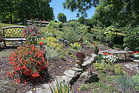 Slopeside hillside landscaping garden with bench, fuchsia in pot container, Oenothera evening primrose, retaining wall, rocks as edging, post and rail fence, mixture of plants, blue sky, evergreens, trees, wide scene view, lawn grass