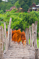 Thailand, Mae Hong Son. Buddhsist monks cross Su Tong Pae Bamboo Bridge to collect food offerings in town, from Po Sama Temple.