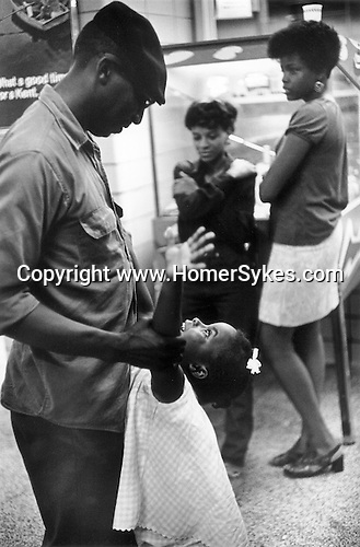 WASHINGTON DC - USA 1969. LATE AT NIGHT IN A GREYHOUND BUS STATION, AN AFRICAN AMERICAN FATHER AND HIS YOUNG DAUGHTER PLAY TOGETHER, WHILE TWO OLDER SISTERS LEAN AGAINST A PIN BALL MACHINE 1960s USA