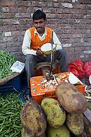 India, Dehradun.  Young Man Selling Jackfruit in a Streetside Market.