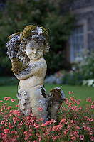 The weathered curly hair and load of grapes of this whimsical bacchanalian statue in the garden have become overgrown with moss