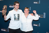 """French film director Francois Ruffin (L), wearing a t-shirt with the portrait of chairperson and CEO of French industrial group Bollore Group Vincent Bollore, poses with a guest during a photocall after winning the Best Documentary Feature award for """"Merci Patron"""" (Thanks Boss) during the 42nd edition of the Cesar Ceremony at the Salle Pleyel in Paris on February 24, 2017."""