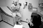 Middle age male patient seated on examination table listening to young female doctor