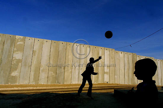 Ishak Amer (C) , 12, a Palestinian boy from the West Bank town of Masha, plays with his young brother Shadad, 3, football in the front yard of their home, in front of a security wall built by Israel, October 28, 2003. The house of the Amer's family is the only Palestinian house of Masha who was left on the Israeli sade of the new security fence, next to the Jewish settlement of Elkana.