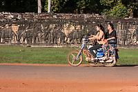 Cambodia, Angkor Thom.  Women on Motorbike Passing the Elephant Terrace.