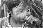 Summer '98-- Jakarta, Indonesia -- A 5yr. old boy looks out on the street after working to collect scrap metal to help pay for food for the family.