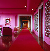 A red carpet runs through a bright pink reception room on the ground floor of the hotel