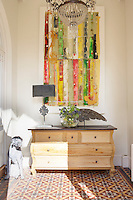 A contemporary artwork hangs above a light wood sideboard, which stands in a recess with a patterned tiled floor.
