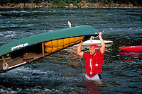 A canoeist in proper gear holds end of canoe to dump water into river. Harrisburg Pennsylvania United States Susquehanna River.