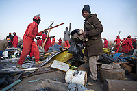 A resident grabs what he can as the Red Ants evict people and destroy an informal settlement near Pomona. <br />The Red Ants are a controversial private security company often hired to clear squatters from land and so-called 'hijacked' properties.