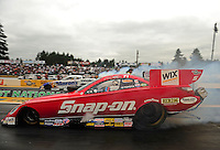 Aug. 5, 2011; Kent, WA, USA; NHRA funny car driver Cruz Pedregon (near lane) does a burnout alongside Jack Beckman during qualifying for the Northwest Nationals at Pacific Raceways. Mandatory Credit: Mark J. Rebilas-