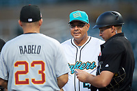 Salt River Rafters manager Keith Johnson (21), of the Miami Marlins organization, meets with Mike Rabelo (23), of the Detroit Tigers organization, and home plate umpire Paul Clemons during the lineup exchange before an Arizona Fall League game against the Mesa Solar Sox on September 19, 2019 at Salt River Fields at Talking Stick in Scottsdale, Arizona. Salt River defeated Mesa 4-1. (Zachary Lucy/Four Seam Images)
