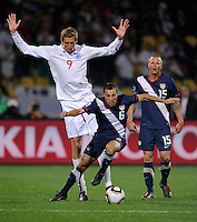 Steve Cherundolo (6) of USA dribbles haead of Peter Crouch (9) of England and Jay DeMerit (15). USA tied England 1-1 in the 2010 FIFA World Cup at Royal Bafokeng Stadium in Rustenburg, South Africa on June 12, 2010.