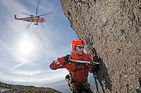 Rescue paramedic Lars Markengbakken working on a bolt that is being used to secure him to the rock face. <br /> <br /> Crew from Norwegian Air Force 330 squadron, flying Westland Sea King helicopter. The core mission of the squadron is SAR (search and rescue), but they also fly HEMS (Helicopter Emergency Medical Service), complementing the civilian air ambulance service.<br /> This crew fly out of Rygge Air Station, Norway.