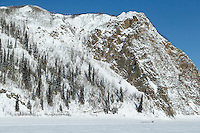 Anna Berington runs past cliffs and Koyukuk Mountain just prior to the Koyukuk checkpoint on the afternoon of Sunday  March 15, 2015 during Iditarod 2015.  <br /> <br /> (C) Jeff Schultz/SchultzPhoto.com - ALL RIGHTS RESERVED<br />  DUPLICATION  PROHIBITED  WITHOUT  PERMISSION