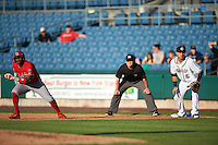 Syracuse Chiefs first baseman Matt Skole (16) holds baserunner Carlos Triunfel (27) on with umpire Jonathan Bailey looking on during a game against the Louisville Bats on June 6, 2016 at NBT Bank Stadium in Syracuse, New York.  Syracuse defeated Louisville 3-1.  (Mike Janes/Four Seam Images)