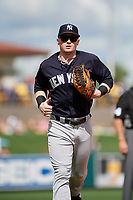 New York Yankees left fielder Clint Frazier (77) jogs back to the dugout during a Grapefruit League Spring Training game against the Detroit Tigers on February 27, 2019 at Publix Field at Joker Marchant Stadium in Lakeland, Florida.  Yankees defeated the Tigers 10-4 as the game was called after the sixth inning due to rain.  (Mike Janes/Four Seam Images)