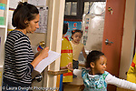 Preschool New York City ages 4-5 female teacher taking notes as children play dressup and pretend play horizontal
