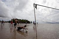 Moradores aproveitam a maré baixa para jogar futebol nas diversas praias que se formam a beira do rio Amazonas. O futebol na lama, conhecido como futelama atrai  peladeiros à orla da cidade.<br /> Macapá, Amapá, Brasil.<br /> Foto Paulo Santos<br /> 11/05/2014