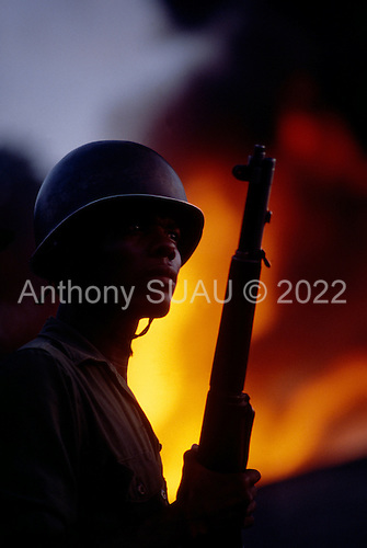 Port-au-Prince, Haiti<br /> November 26,1987<br /> <br /> Guarding a fire set to disrupt the elections to be held on November 29th, the first attempt at a democratic election in Haiti. It was unsuccessful as 34 people were killed at a polling station and elections were moved up to February 1988.<br /> <br /> Leslie François Manigat won the election with many political parties boycotting. He had military backing but once in office he sought greater control over the military in an effort, to fight corruption. Manigat's government was overthrown by General Henri Namphy within months.