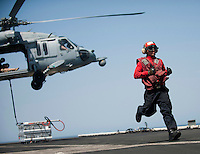 120330-N-DR144-552 ARABIAN SEA (March 30, 2012) Aviation Ordnanceman Airman Edward Pyzik runs to clear the area after attaching crates of ordnance to an MH-60S Knight Hawk during an ordnance transfer aboard the Nimitz-class aircraft carrier USS Carl Vinson (CVN 70). Carl Vinson and Carrier Air Wing (CVW) 17 are deployed to the U.S. 5th Fleet area of responsibility.  (U.S. Navy photo by Mass Communication Specialist 2nd Class James R. Evans/Released)