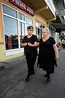 Women dressed in black walk through Batumi.