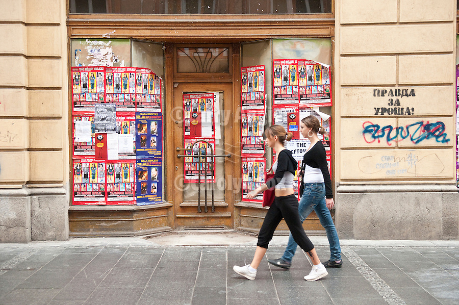 Teen girls walk by a building entrance covered with handbills in Belgrade, Serbia.