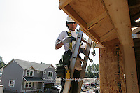Pedro Vargas climbs up to the roof of a new Quadrant Home in Mt. Vernon, Washington on August 4, 2006.