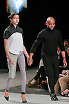 Graduating fashion student Jefferson Musanda, walks runway with model at the close of the 2013 Pratt Institute Fashion Show, on April 25, 2013.