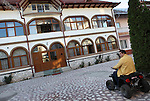 Romania, Tirgu Jiu - Ninel Potirca, one of the wealthiest ROMa people in Romania, riding his ATV in front of his mansion.