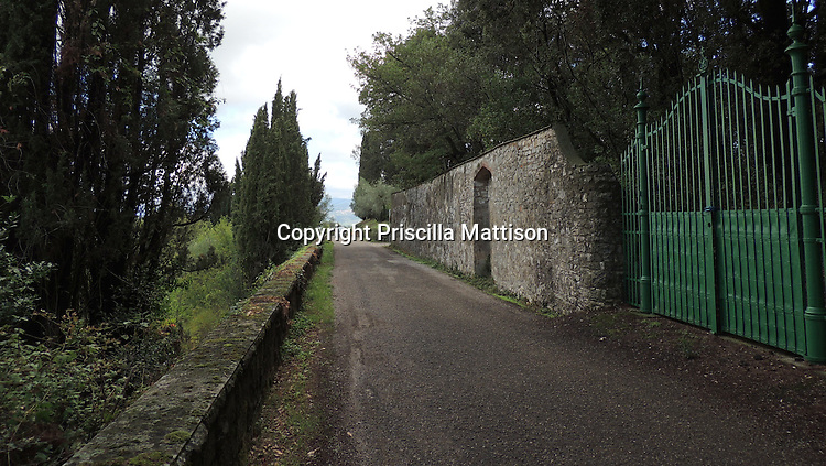Val d'Arno, Italy - October 2, 2012:  A green gate is set into a stone wall along a Tuscan road.