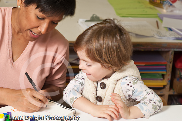 Education preschool 3-4 year olds female teacher scribing for 2 year old writing down what she says is in her drawing horizontal