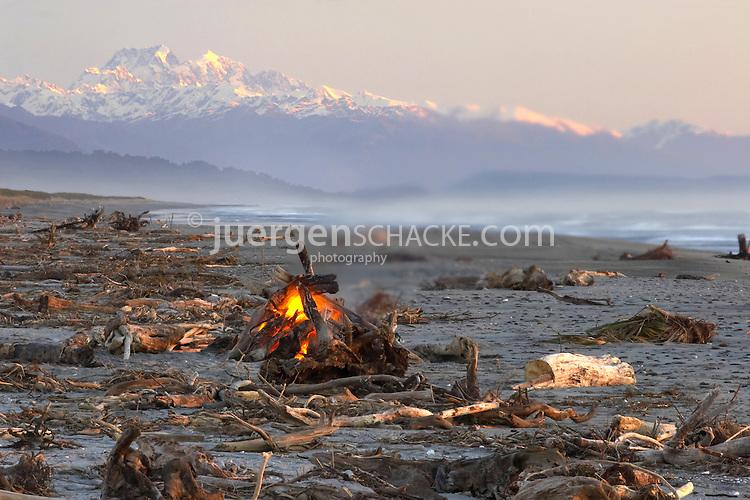 bonfire on beach just south of Hokitika with view of Aoraki Mt.Cook and Mt.Tasman