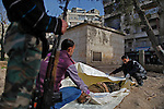 """Hisham (at right) and Free Syria Army civilian volunteers prepare a body for burial at Martyr's park (formerly known as Cobbler's Park) in the Bustan Al-Qasr neighborhood of Aleppo. ..The park, under Free Syria Army control,  has been renamed """"Martyr's Park""""  since the revolution arrived in Aleppo in July of 2012.  A patch of dirt that lies next to children's swings, slides and monkey bars now serves as this neighborhood's makeshift cemetery. On January 29, 2011, 110 bodies floated down a water canal (which is part of the river Qweiq) that separates this rebel-controlled area from the regime side on the opposite side of the canal. Many of the showed signs of torture and most where executed with their hands bound behind their backs. In the weeks after this incident, dozens more bodies have been discovered in the canal - many of the victims that have not been claimed by family members have been buried here."""