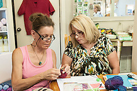 STAFF PHOTO ANTHONY REYES • @NWATONYR<br /> Loralee Canfield, left, owner of the Mockingbird Moon, helps Carol Vick, of Rogers, with a knitting project Thursday, Sept. 18, 2014 during a crocheting and knitting class at Mockingbird Moon in Rogers.