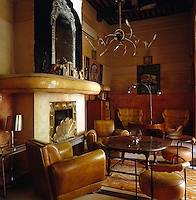 """1920s leather chairs and Joe Colombo """"Elba"""" chairs fill this sitting area which features a brass-detailed fireplace"""