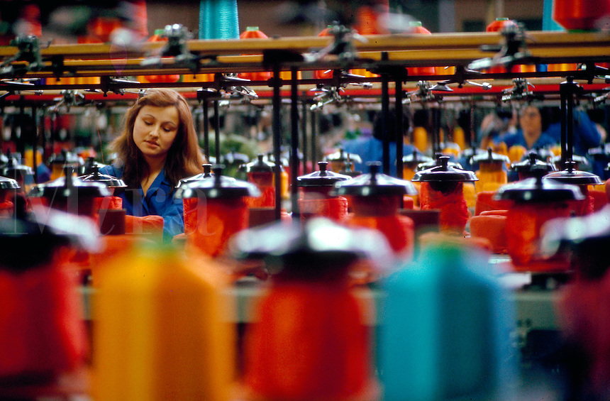 A female worker amongst thread during textile manufacturing.