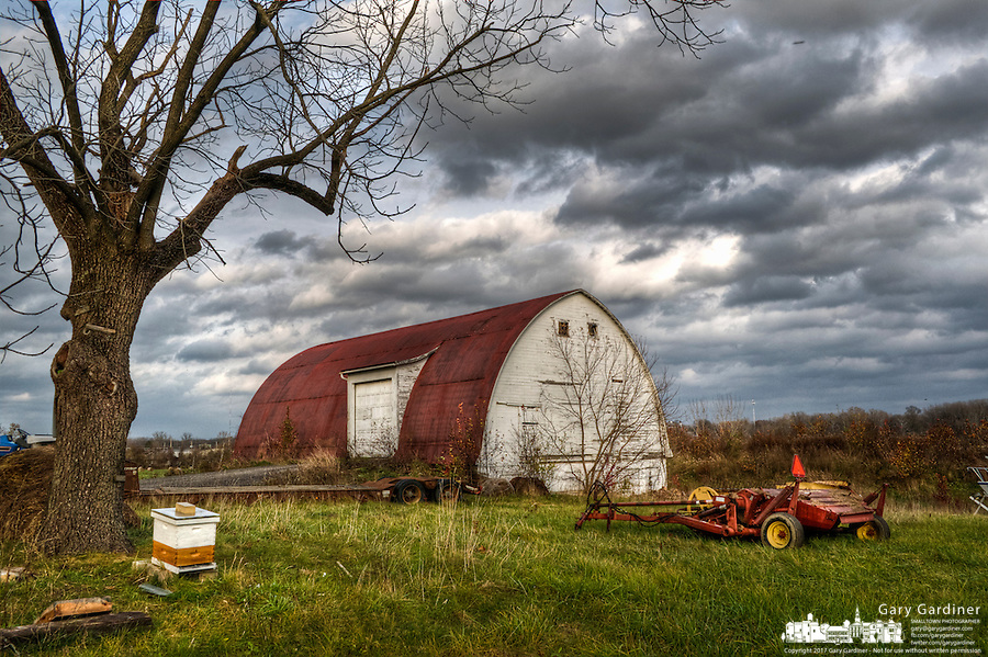 Heavy storm clouds blown by strong November winds move over the barn on farm land along Cleveland Avenue at Cooper Road. One of the farm's bee hives sits beneath a tree bared of its leaves in the fall. At right is a hay used on the farms hay fields.