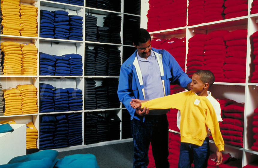 AFRICAN-AMERICAN FATHER AND SON IN A RETAIL STORE BUYING A SWEATSHIRT. FATHER AND SON. OAKLAND CALIFORNIA USA.